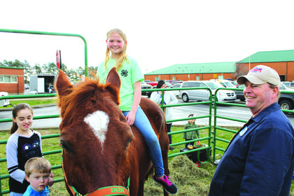 "Abigail Morgan, 9, rides ""Duke"" outside at the LaRue County Extension Expo on March 17 while James Jones of the 4-H Wranglers horse club looks on"