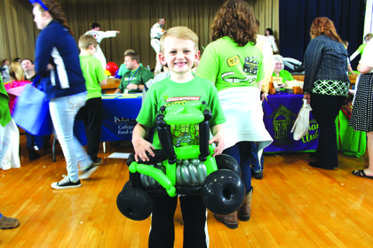 "Avery Bivens, 7, shows off his John Deere balloon art. Held on St. Patrick's Day, this year's theme for the expo was ""Go Green."""