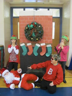 """Hodgenville Elementary School students Keegan Spratt (Santa Claus) falls from the chimney while Blitzen Reindeer (Cruz Lile) points and laughs. Elves Catherine Spalding and Eden Sidebottom show surprise. The students were performing in """"Christmas Through the Ages."""""""