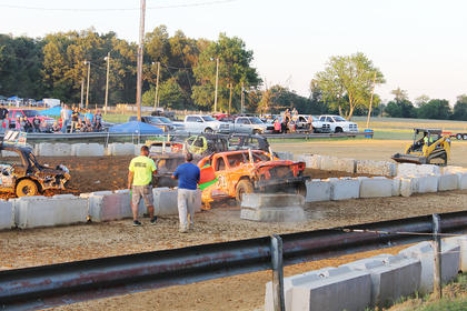 The demolition derby was intense at the fair as one of the cars broke through the concrete barrier