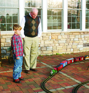 Alex LaRue and his grandson Jameson watched a train complete its route around a Christmas tree at the home of Jim and Susan Phelps. The home was part of the holiday home tour sponsored by the Hodgenville Woman's Club.