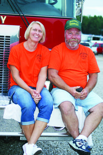 """Jo and Mike """"Stumpy"""" Mather sat on the bumper of a fire truck as they listened to J.D. Shelburne sing at AGstravaganza."""