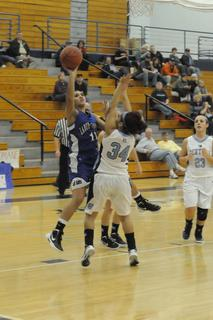 Alexis Brewer puts up a one-handed shot over Central Hardin's Alexis Johnson.