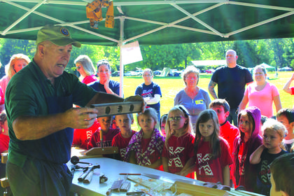 A presenter shows students how to use a level during a woodworking demonstration.  Nearly 800 students and teachers, accompanied by parents and grandparents, from several surrounding school districts participated in the two-day program.
