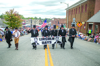 Abraham Lincoln presenters led the parade with the Lincoln Days banner. It is a custom for the presenters to carry the banner at the beginning of the parade each year.