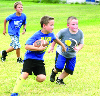 Reed Miller attempted to get by Baines Turner at Football Skills Camp organized by the varsity football coaches and players.