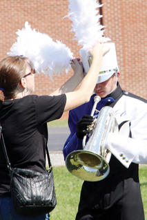 Band of Hawks member Jesse Highbaugh receives some help with his plume before the Taylor County Invitational begins.