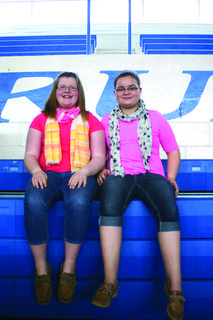 AllyRae Milford, left, and MacKenzie Turner sat in the bleachers overlooking the booths at Extension Expo.