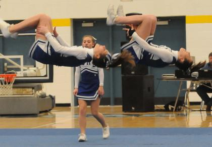 LaRue County Middle School cheerleaders Gabby Garcia and Rachel Armes perform tucks during their competition.
