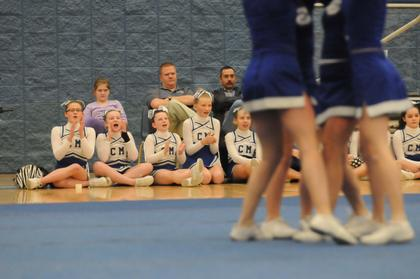 The middle school cheerleaders cheer for the varsity squad.