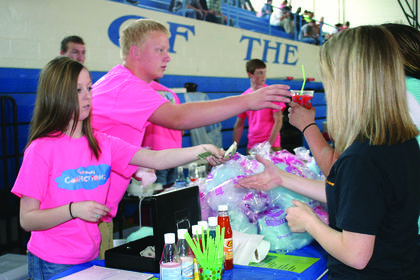 """Olivia Nalley, left, and Wyatt Long sold slushies and cotton candy at the """"Snowy Confections"""" booth."""
