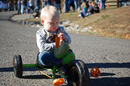 Remington Faulkner, 1, rides a child's bike near the finish line of the race in memory of his grandfather Ed Faulkner. Since Ed's passing in 2016, the Faulkner family continues to attend the event every year.