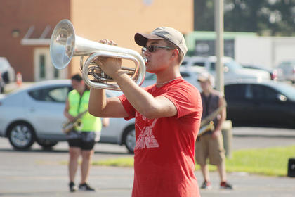 Baritone player Parker Smith holds his horn up high during practice at summer camp.