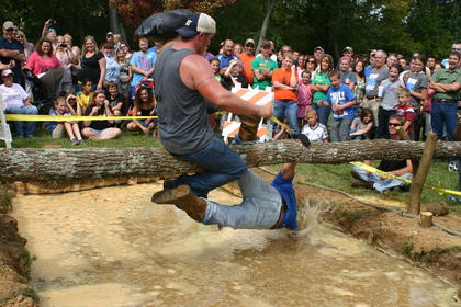 Tyler Adams takes a plunge into the muddy pit of water after being defeated by Jason Nunn in the men's pole ride competition.