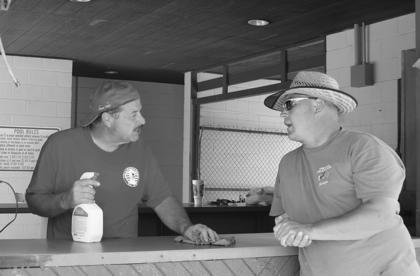Hodgenville Mayor Terry Cruse cleaned the counter at the pool's concession stand while he spoke with Park and Recreation Manager Paul Newell.