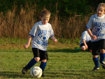 Evan McCreery ran the ball down the field at a U8 soccer game.