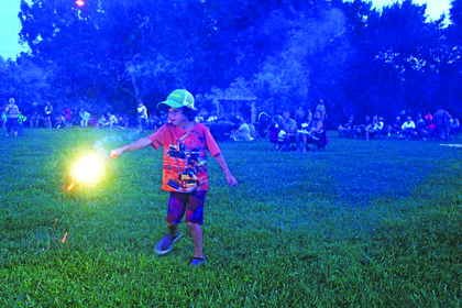 Braydin Malcomson is pictured celebrating independence day with a sparkler.