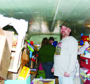 Long-time Santa's Helper Tommy Morrison collected toys on the Santa Bus as children waited outside.