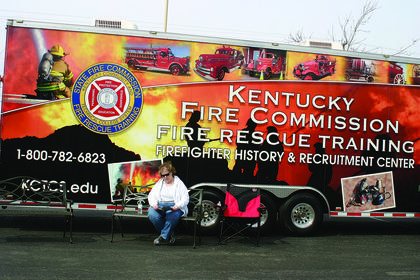 "Marcia Cox looked over a pamphlet while sitting outside the Kentucky Fire Commission's trailer at Saturday's Expo. This year's focus was ""emergency preparedness."""